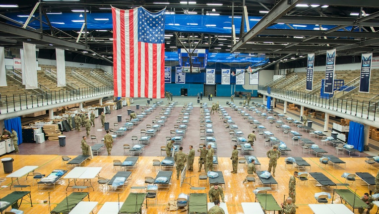 National Guard troops set up medical equipment inside a college sports arena