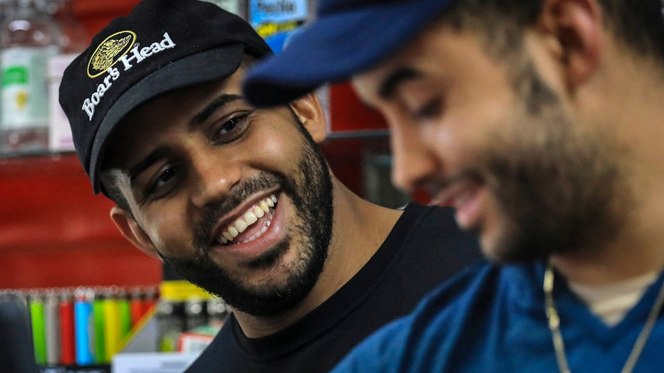 Brothers Alex Batista and Eudis Batista smile as they work at their deli