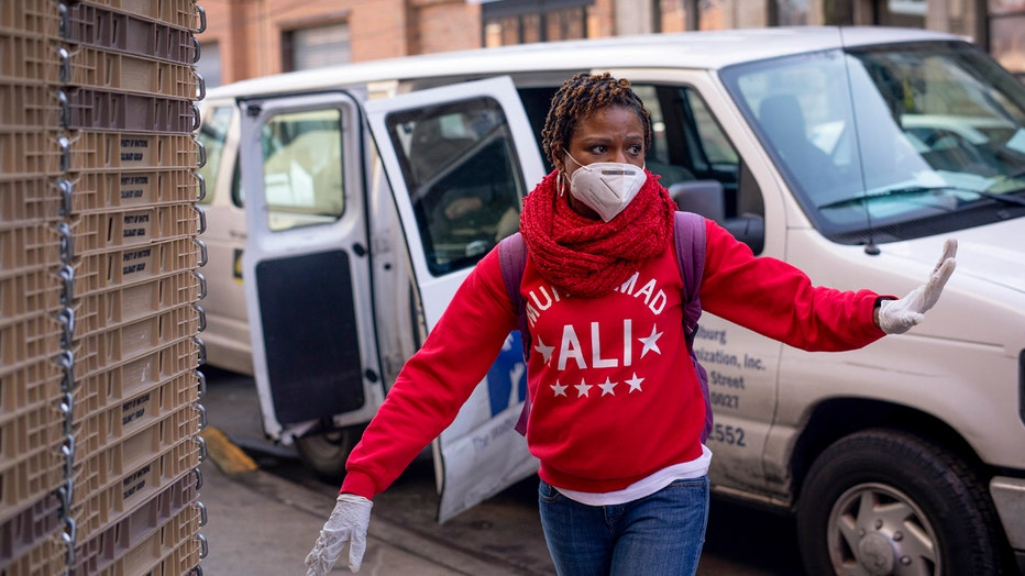 Carla Brown, wearing a mask, holds out a gloved hand