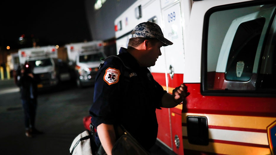 Paramedic Travis Kessel holds the door of an FDNY ambulance