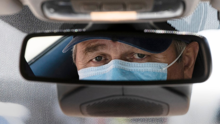 Taxi driver Nicolae Hent's face seen in rearview mirror