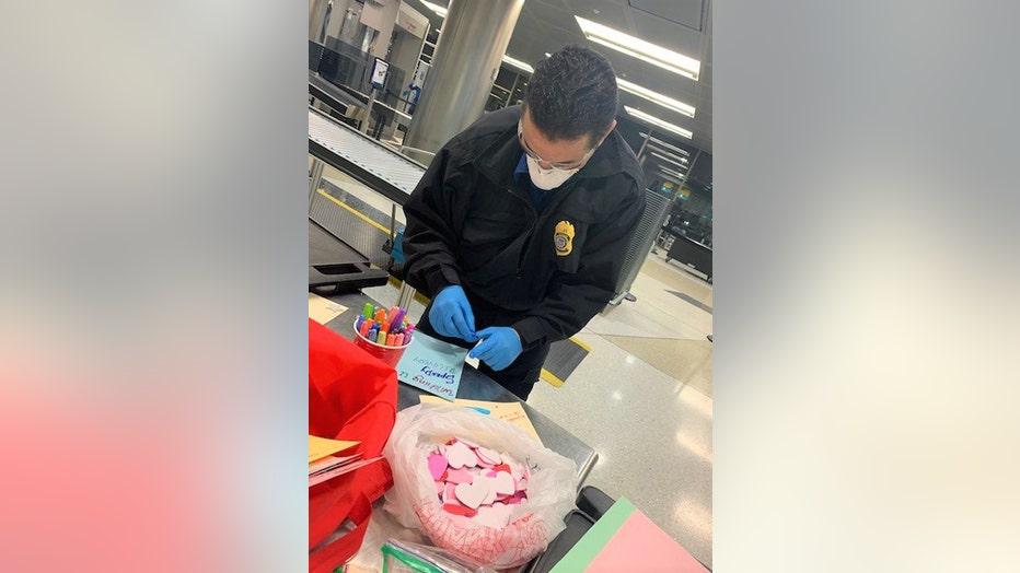 TSA officer wearing a mask makes a greeting card