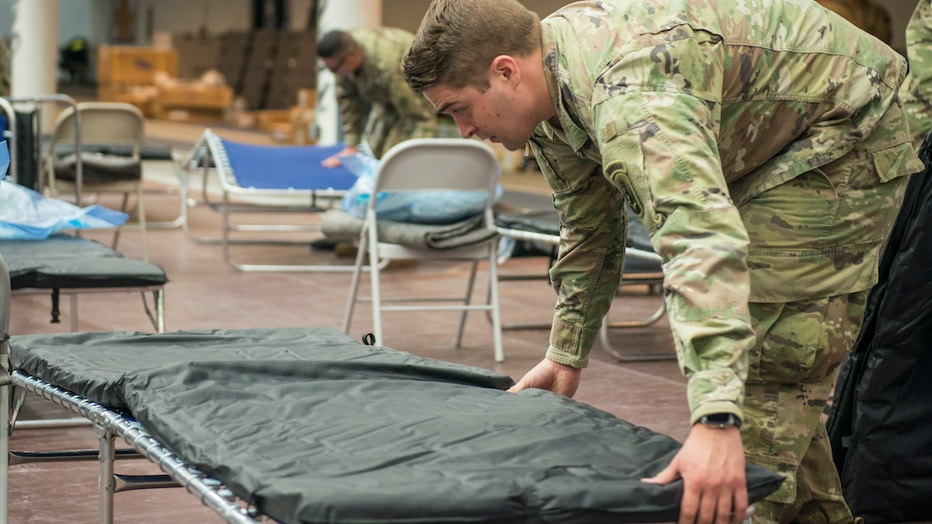 Soldier sets up a field hospital bed inside a college sports arena