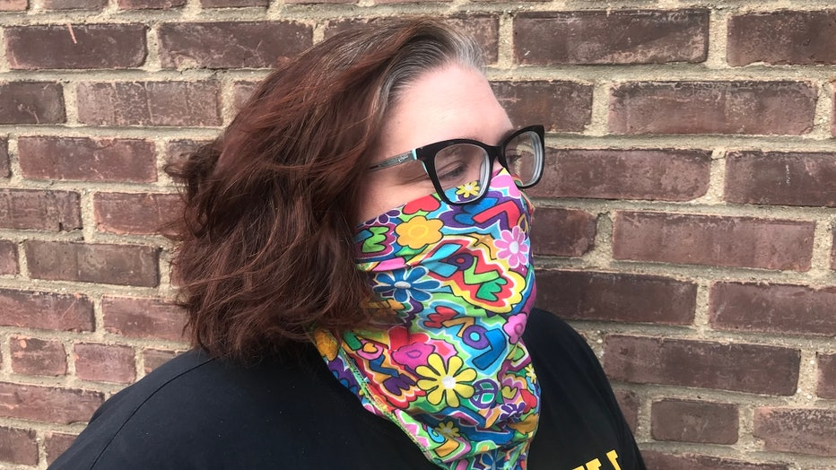 A woman wears a colorful bandana