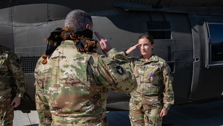 A soldier wearing a Purple Heart medal salutes a superior officer