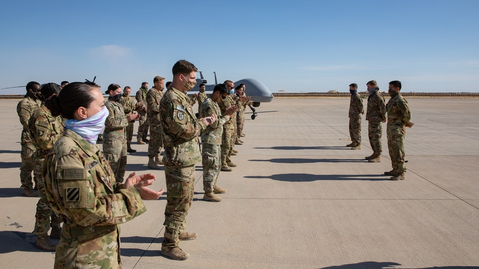 Soldiers clap for fellow service members on a base