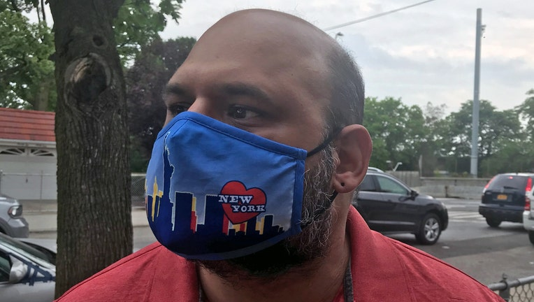 Man wearing a multicolored fabric mask over his face
