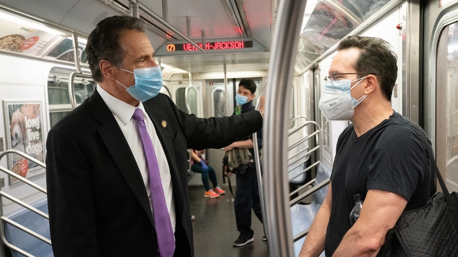 Governor and subway rider stand facing each other inside a subway car