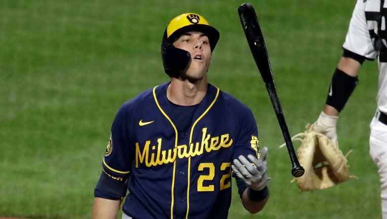 Wearing a blue and yellow Brewers uniform, Christian Yelich flips his bat