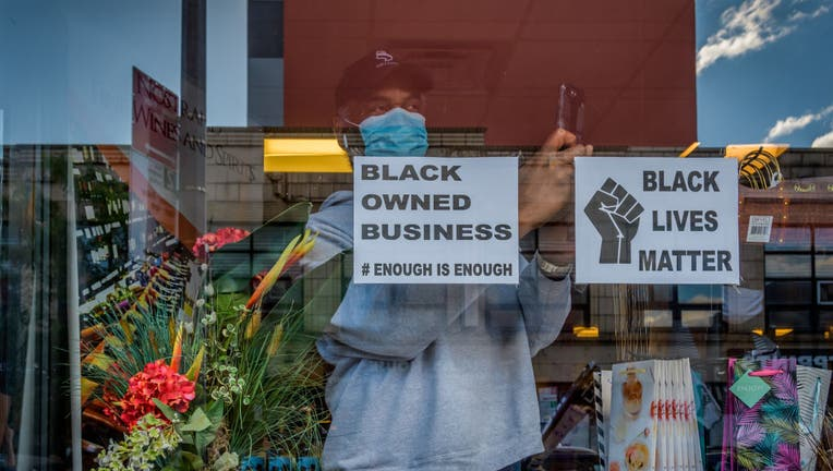 Open storefront displaying a Black Owned Business sign.