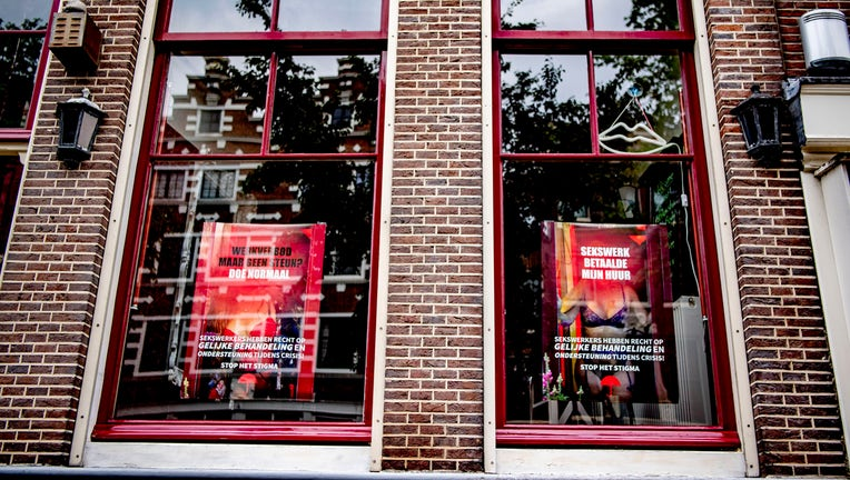 Posters for sex workers in windows of a brick building in Amsterdam