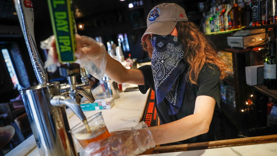 Bartender wearing a baseball cap on her head and a bandanna over her face pours beer into a cup at a bar