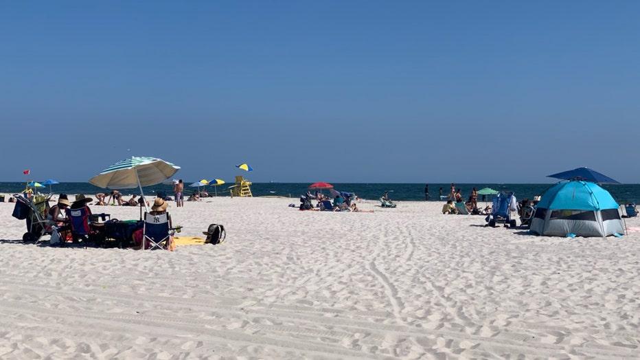 Beachgoers on towels and under umbrellas looking toward the Atlantic Ocean