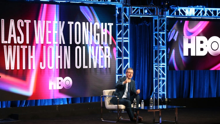 John Oliver sits on stage with large monitors behind him displaying Last Week Tonight with John Oliver and HBO