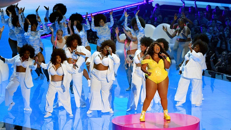 Lizzo in a yellow outfit sings on stage with a group of performers behind her