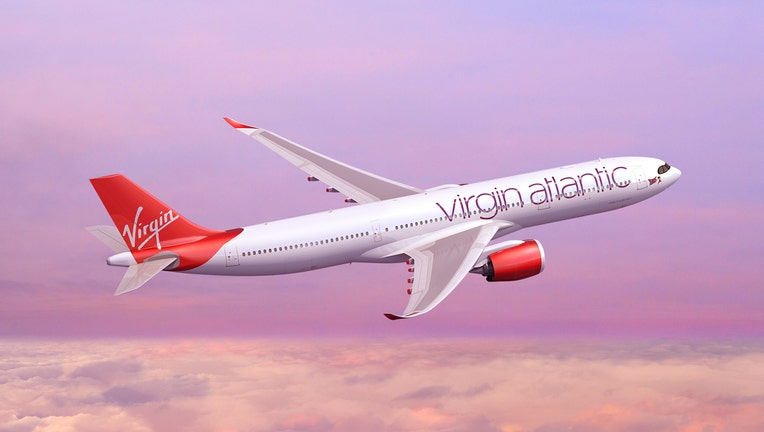Red and white Virgin Atlantic jetliner flying above the clouds