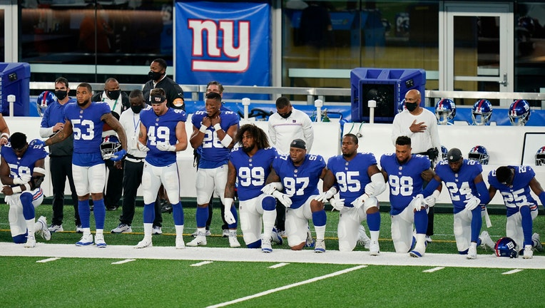 Giants football players in blue and white uniforms; some stand, some kneel on the field