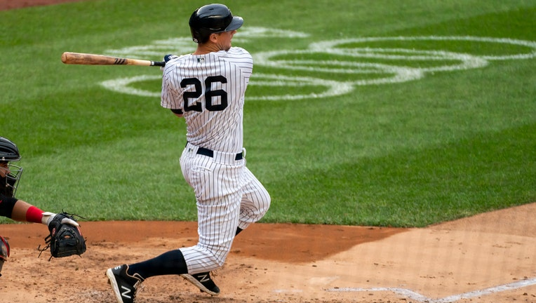 Player in blue-and-white Yankees pinstripes swings through after connecting with a baseball