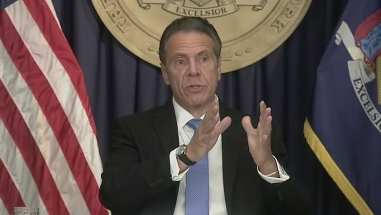 Andrew Cuomo gestures while speaking in front of US and New York flags