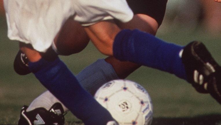 Young boys legs around a soccer ball