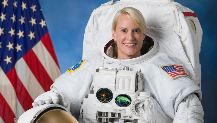A smiling astronaut in a white space suit with American flag behind her