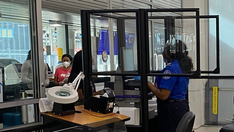 Clear barriers protect a TSA officer