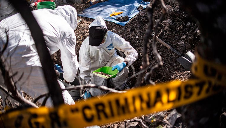 Forensic personnel work in the exhumation of human remains found in Huitzuco de los Figueroa, Guerrero state, Mexico.