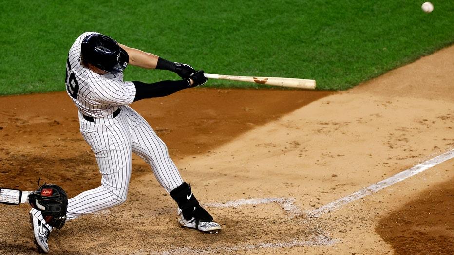 Player in blue-and-white Yankees pinstripes swinging baseball bat