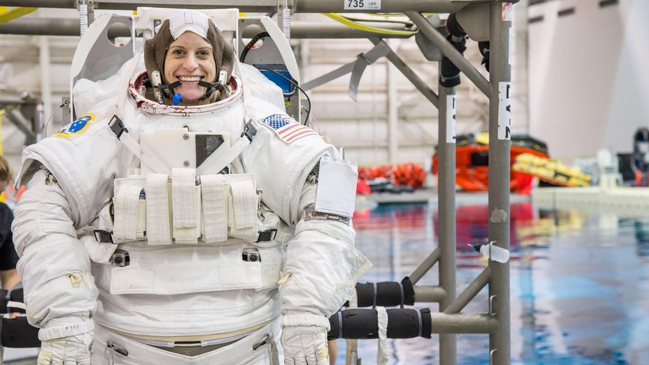 An astronaut in a bulky suit next to a pool