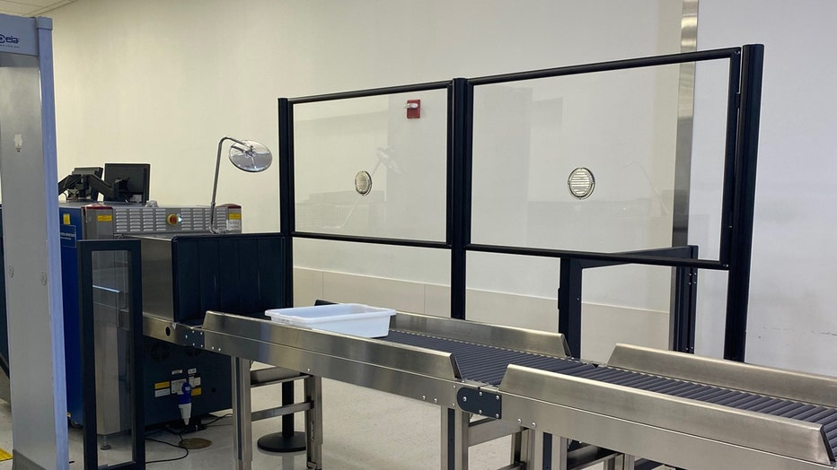 Clear barriers installed next to airport X-ray screening machine