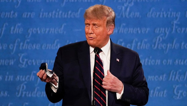 Trump holds a face mask in his right hand as he stands on the debate stage in front of a blue backdrop