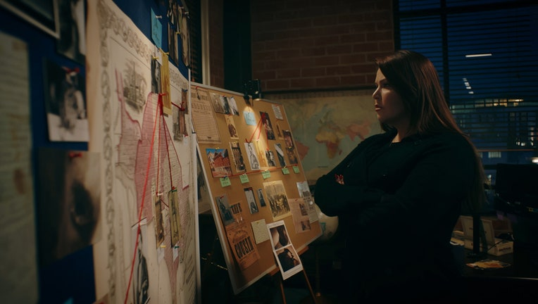 A woman looks at photos and other items pinned to display boards in an office