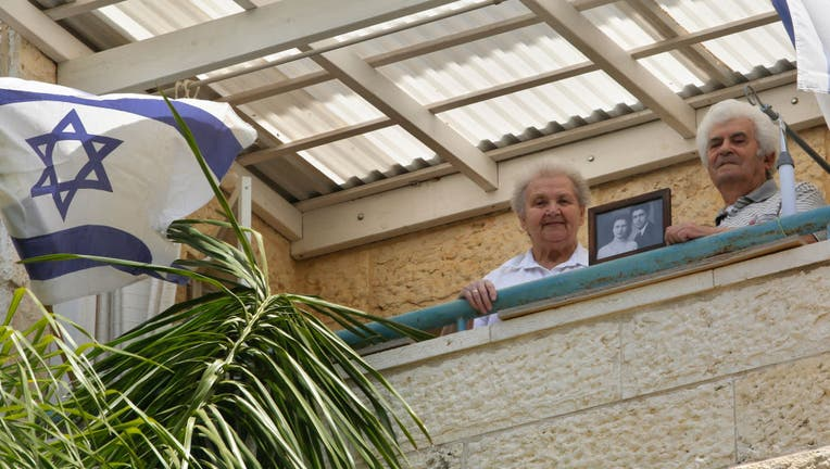 MODIIN, April 21, 2020 -- Holocaust survivors Dmitry Kazavchinski R, 85, and his wife Svetlana, 80, display a picture at their own house amid the COVID-19 pandemic in the central Israeli city of Modiin on April 21, 2020.