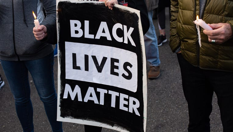 A person holds a Black Lives Matter sign (Photo by David Ryder/Getty Images)