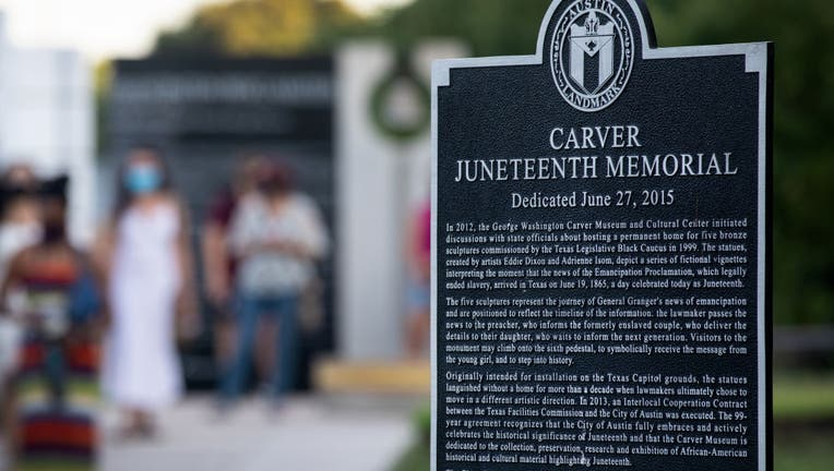 A sign dedicated to information about the Carver Juneteenth Memorial.