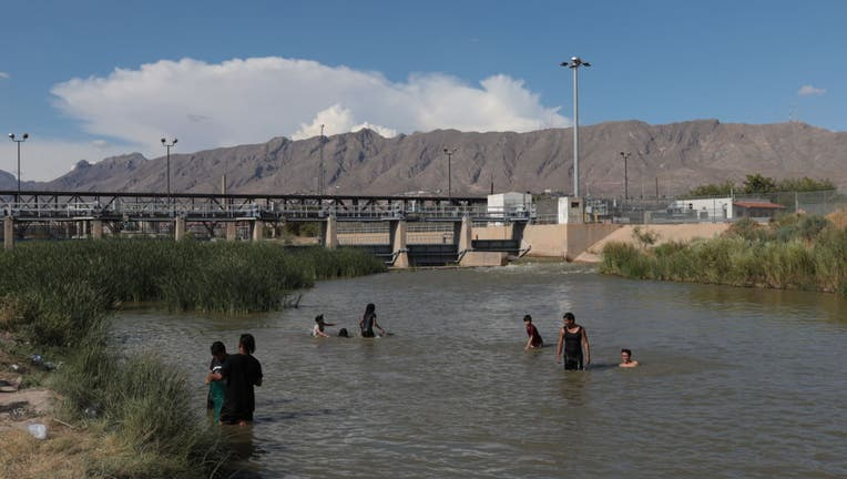Young people, play in the water of the Rio Grande.