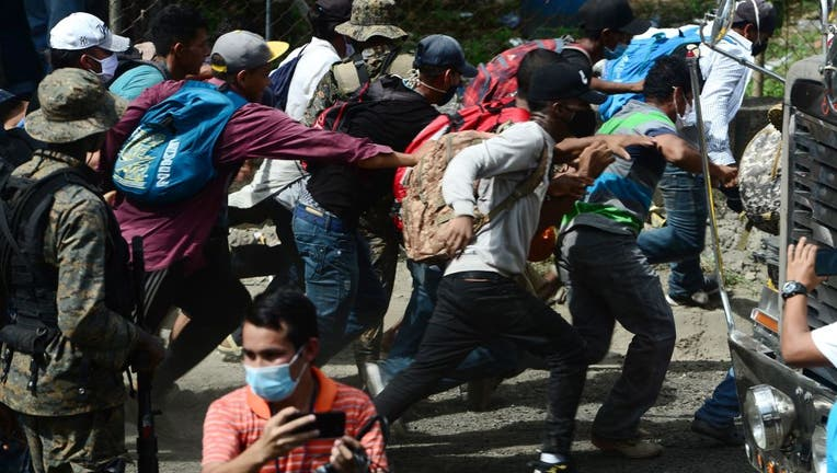 Migrants break a police fence to enter Guatemala on the way to the US.