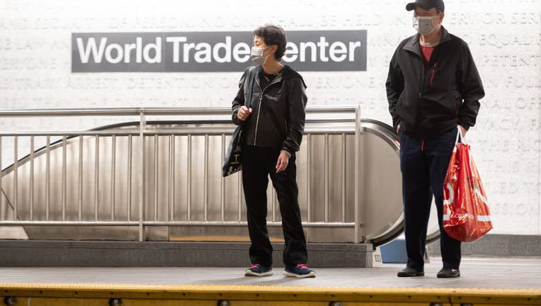 FILE People wear protective face masks at the subway platform in the World Trade Center transportation hub.