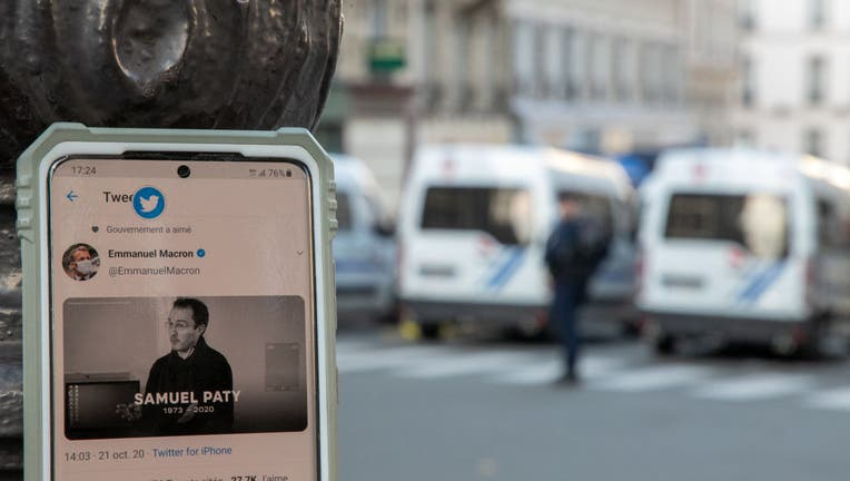 A close-up at French President Emmanuel Macron's official twitter account showing a picture of Samuel Paty as police are deployed around Sorbonne University during a national tribute to the slain teacher on October 21, 2020 in Paris, France.