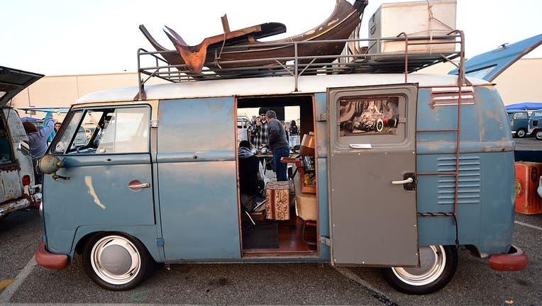 People make trades on parts beside a 1959 Volkswagen Kombi.