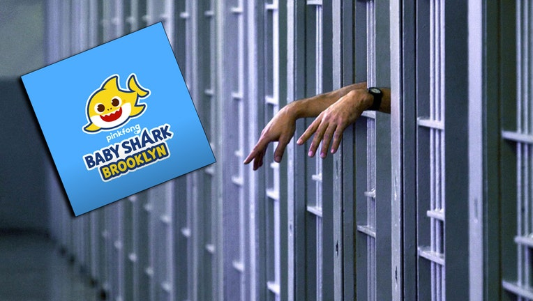 Inmate's hands visible through bars in a jail cell; colorful logo of Baby Shark