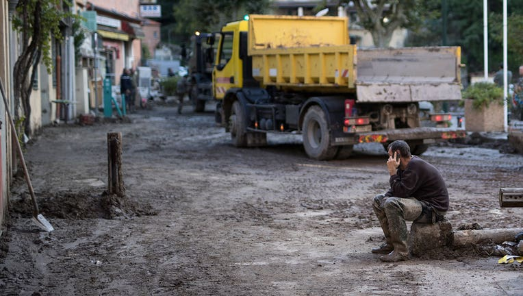 A resident takes a break from clearing mud from a property, in Breil-sur-Roya, near the border with Italy, Monday, Oct. 5, 2020. Flooding has devastated mountainous areas in France's southeastern region of Alpes-Maritimes and Italy's northwestern regions of Liguria and Piedmont, after a storm swept through the two countries on Friday and Saturday. (AP Photo/Daniel Cole)