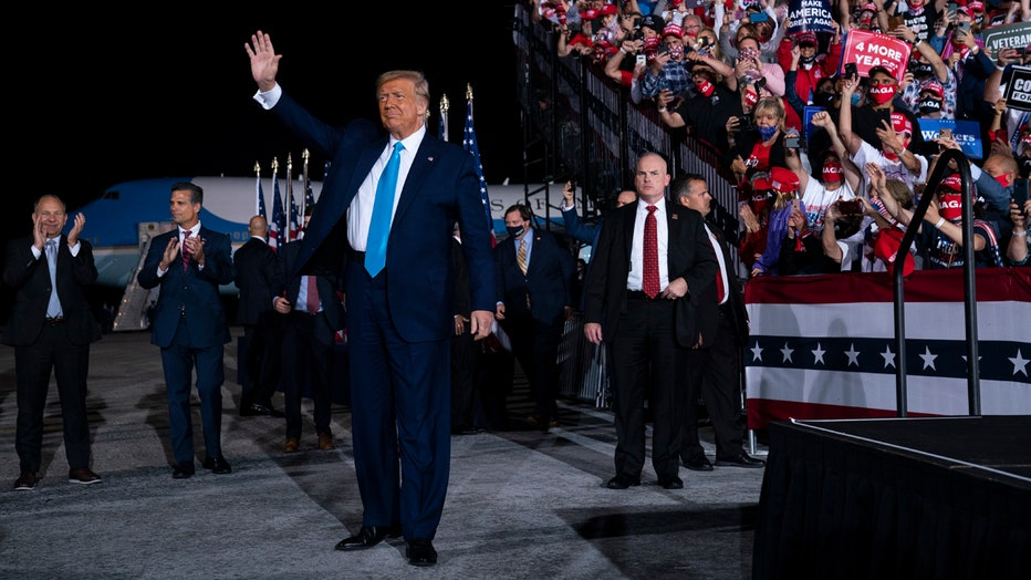 Donald Trump waves at a rally; in the background are supporters in bleachers, security personnel, staff, American flags, Air Force One