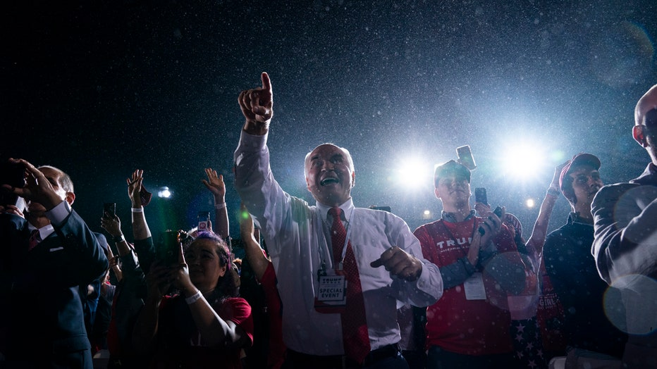 Several people wave and cheer at a nighttime campaign rally