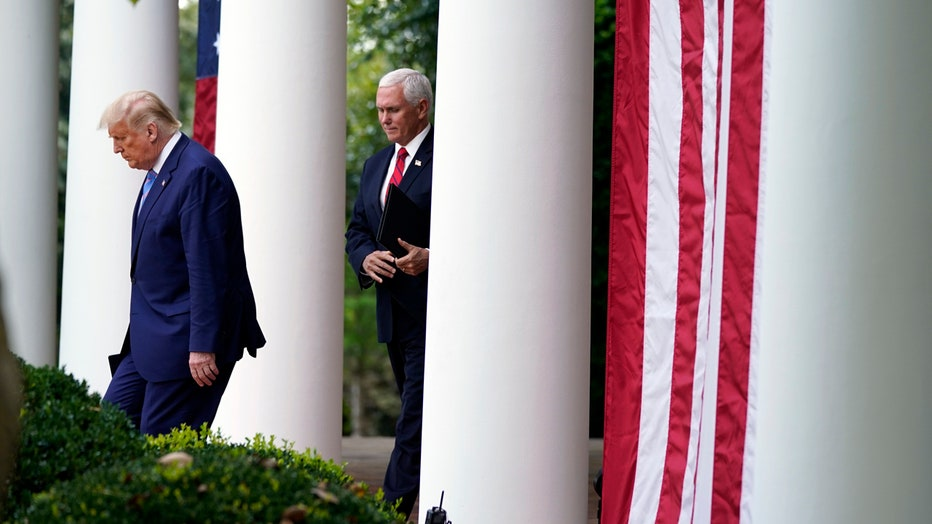 Trump and Pence walk in between some columns and bushes at the White House