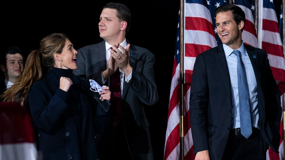 Hope Hicks, holding a mask, cheers and makes a fist gesture at a rally; three men and some American flags are visible