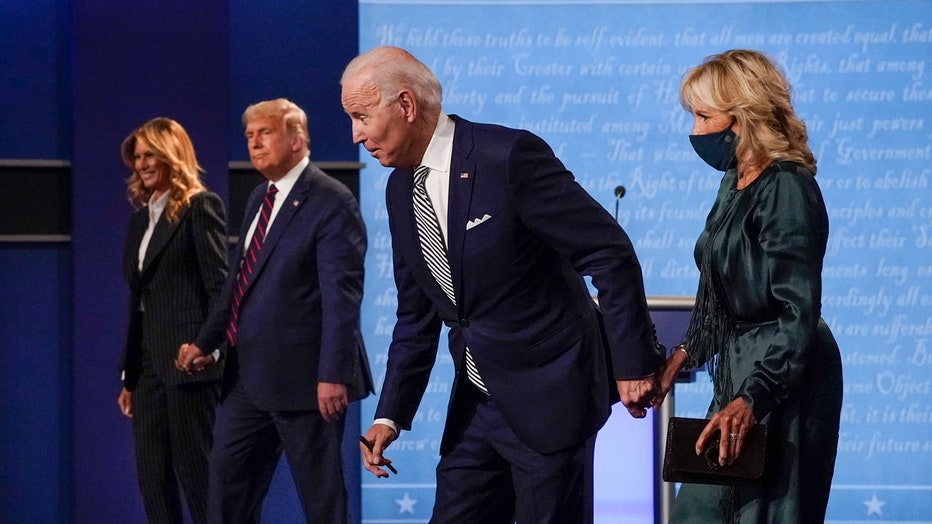 Melania Trump, wearing a striped suit, and Donald Trump, wearing a blue suit and a blue-and-red tie, hold hands; Joe Biden, wearing a blue suit and a blue-and-white tie, and Jill Biden, wearing a sage-green outfit, hold hands