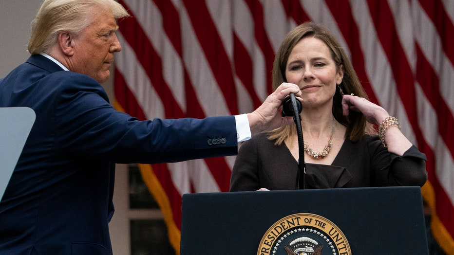 Trump touches a microphone on a lectern in front of Judge Amy Coney Barrett
