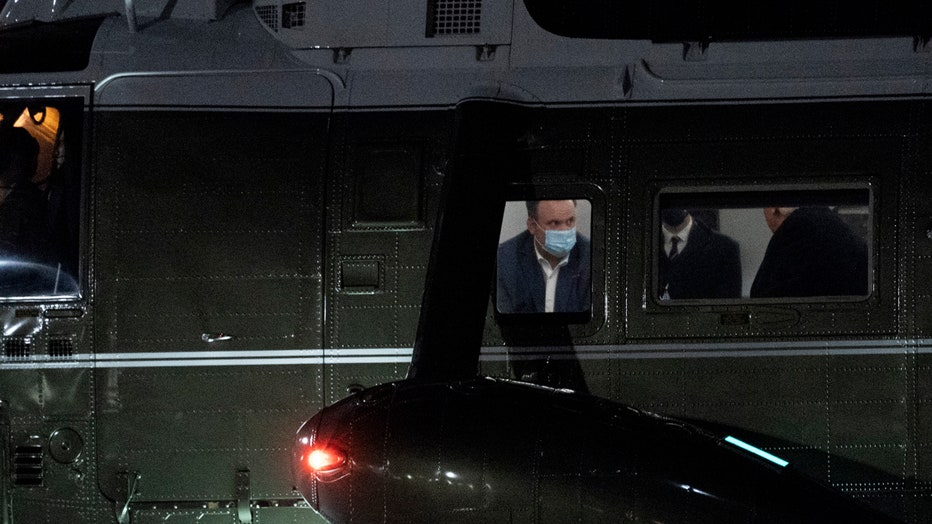 Three people are seen through windows of the Marine One helicopter; one of the people, Dan Scavino, is wearing a light blue mask