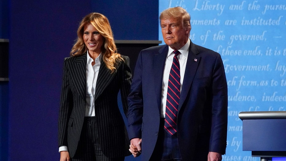 Melania Trump, wearing a striped suit, smiles as she holds Donald Trump's hand on stage; the president is wearing a blue suit and a blue-and-red tie